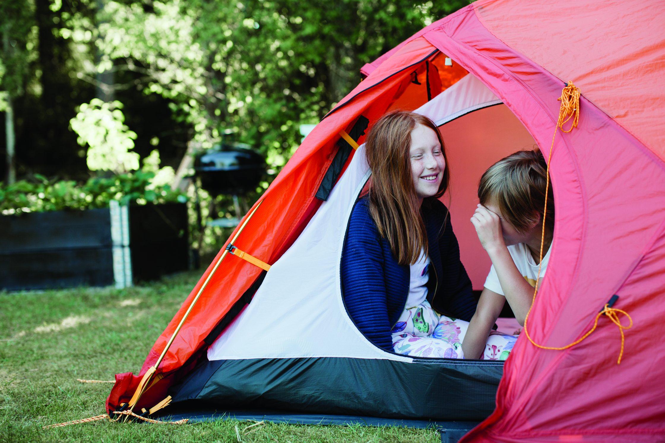 Två barn som sitter i ett tält.