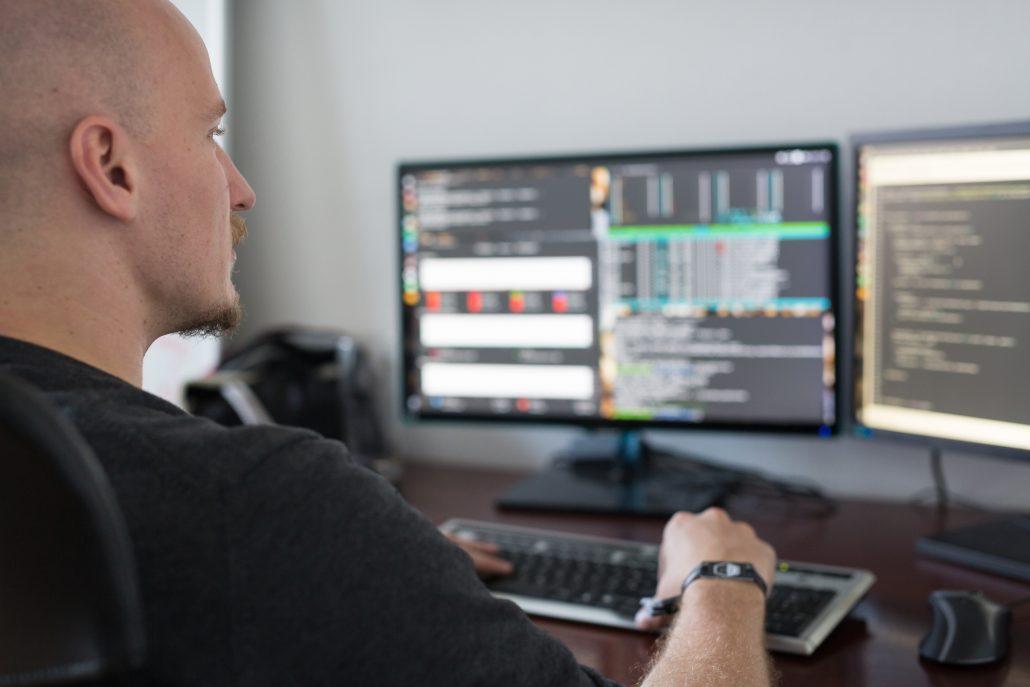 Kille som sitter och programmerar framför en dator