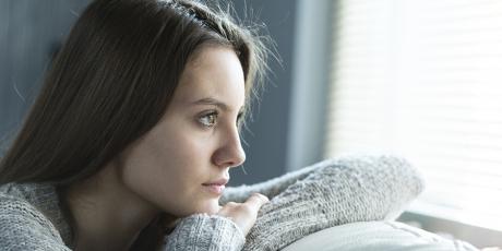 Bild på kvinna som tittar ut genom ett fönster.