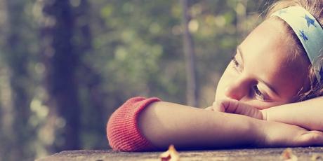 Barn som vilar sitt huvud mot sina händer.