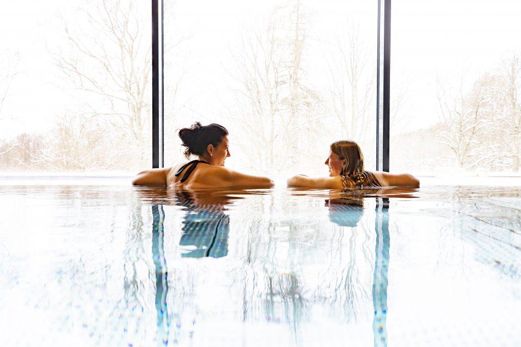 Bild på två personer som badar.