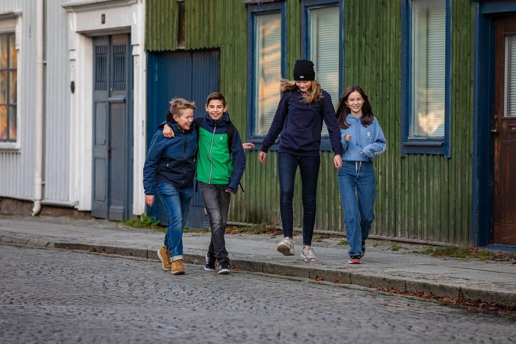 Fyra ungdomar som går bredvid varandra och skrattar.