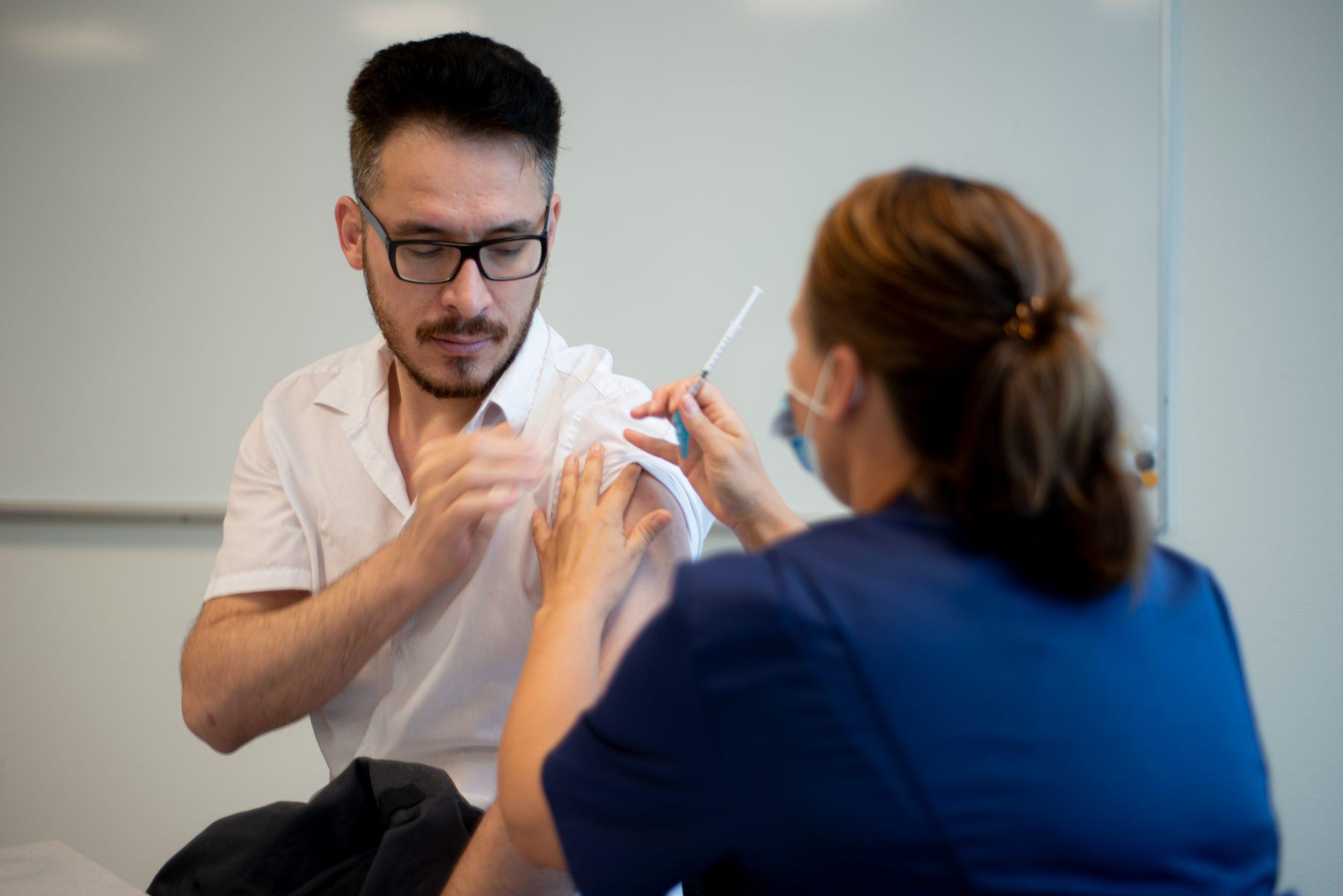Student på Campus Alingsås får en spruta av vaccinationssköterskan Sara.